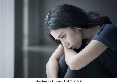 Close up of a sad woman suffering anorexia while sitting in the black background