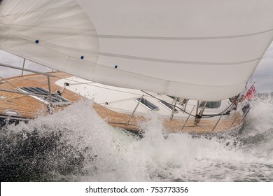 Close up of sailing boat, sail boat or yacht crashing through waves in a rough sea