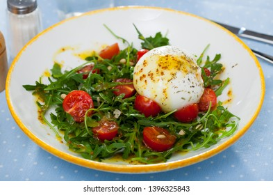Close up of salad with burrata cheese, pine nuts, cherry tomatoes and arugula with spice at  plate
