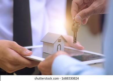 Close up salesman holding home key to business sale estate rent concept