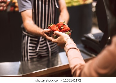 Close up salesman in striped apron behind counter giving strawberries to customer in modern supermarket
