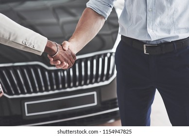 Close up of salespeople, moving in hands with a male African customer after the sale of a new car