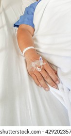 close up of saline solution preparation on hand of man patient lying on the hospital bed