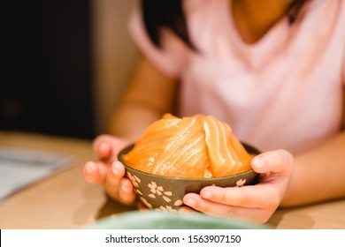 Close up salmon sashimi with rice.Little girl hands holding fresh salmon and ready to eat in Japanese restuarant. Healthy eating seafood.Japanese food.Happy meal and Delicious asian food concept.
