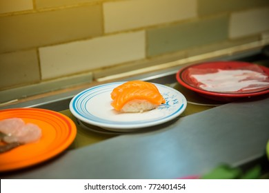 Close up salmon sushi on dish in belt japanese food buffet. trendy popular restaurants. healthy food type of boiled instead fried trans-fat. image for background, objects and copy space.