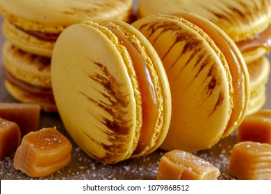 Close up of salted caramel flavored french macarons surrounded by bits of caramel and sea salt