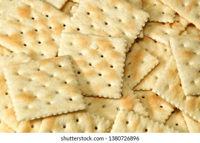 Close up of saltine crackers filling entire image, also known as soda and soup crackers.