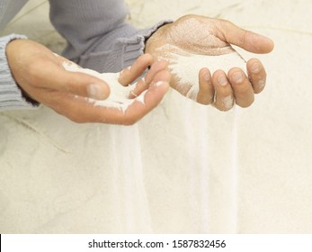 Close up of sand pouring through man's hands