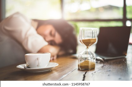 Close up of sandglass with business woman tired from working with laptop computer background. Relax Sleeping and taking nap concept. Business people and overtime workload theme. Office and home theme