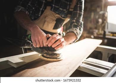Close up of sanding a wood with orbital sander at workshop
