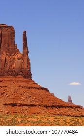 A close up of the sandstone rock formation know as a mitten rises dramatically from the floor of Monument valley in Arizona.