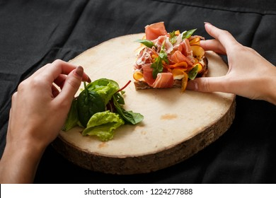 Close up sandwich with jamon and salad on board. Womans hand holding folk and knife. Sandwich with jamon and apple, salad. Delicious lunch. Serving dishes concept. Restaurant food concept