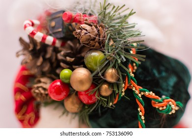 Close up of Santa Claus green velvet Christmas sack. Focus is on red green and gold baubles at the front of sack.