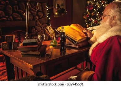 A close up of Santa Claus as he works on his christmas list for who's been bad or good, naughty or nice