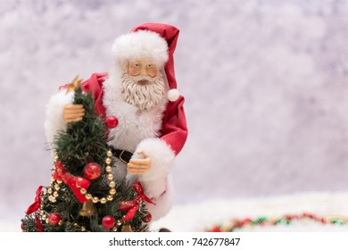 close up of Santa Claus ornament with decorated Christmas tree on a winter Christmas background.