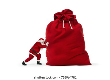 Close up of Santa Claus pushing huge bag of presents isolated on white background