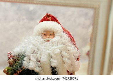 close up of a Santa ornament. Child hands holding a frame around Santa Claus. Father Christmas inside a golden frame with a winter background