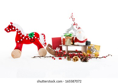 Close up of Santa sitting on wooden horse sledge holding gift and presents - white and red christmas background,  isolated decoration
