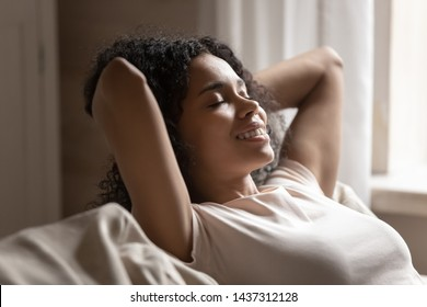 Close up satisfied calm african woman put hands behind head resting daydreaming on sofa, black attractive 30s female spend time at home closed eyes relaxing feels serenity no stress enjoy lazy weekend