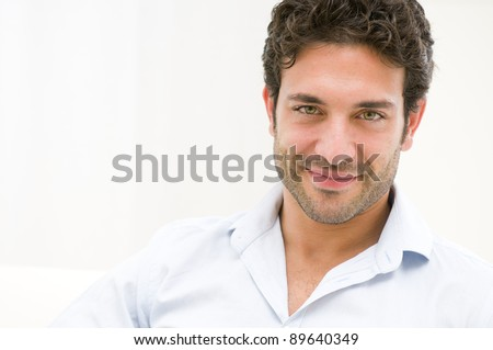 Close up of satisfied smiling guy looking at camera at home