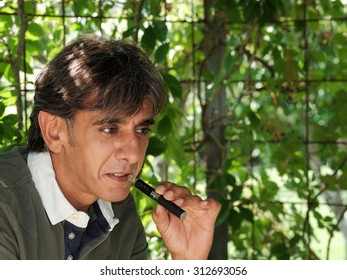 Close up of a satisfied smoker of electronic cigarette in dim light