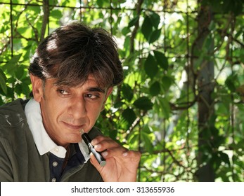 Close up of a satisfied smoker of electronic cigarette with vegetation background