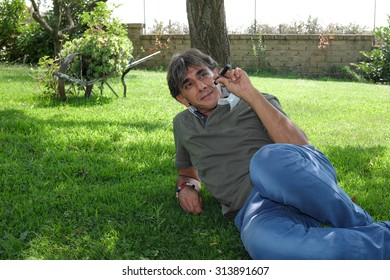 Close up of a satisfied smoker of electronic cigarette lying on green lawn