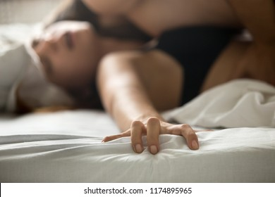 Close up of satisfied woman hand holding bed feeling orgasm having sex with lover, passionate couple making love on white sheets in bedroom, woman moaning with pleasure or ecstasy, enjoying intimacy