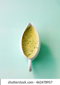 Close up sauce boat with herb sauce hollandaise isolated with copy space