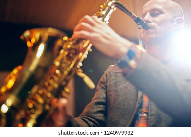 Close up of saxophonist playing his instrument. Back light.