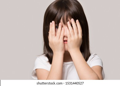 Close up of scared small preschooler girl isolated on grey studio background cover face with hands peep look through fingers, terrified little child peek feel afraid frightened, interest concept