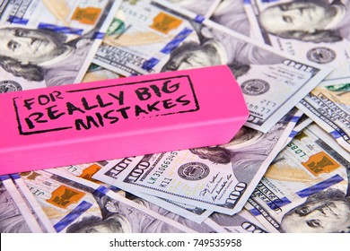 Close up scattered US Dollars with message on pink eraser for really big mistake.  Concept fixing financial, business, taxes, savings, loan mistakes
