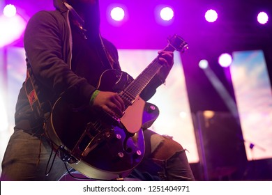 Close up scene of electric guitar player on performing stage during playing solo on concert with colourful scenic illumination via powerful lights. Unicolor simple photography