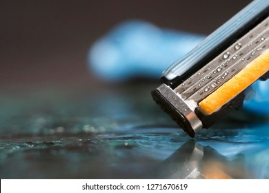 close up scene of razor blades with water drops isolated on dark background.