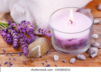 Close up of scented tea light candle with lavender flowers, stones and towel on rustic wood  -  Natural spa scene  -  Wellness
