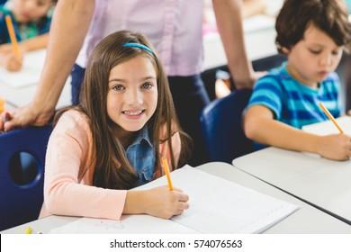 Close up of school girl doing homework in classroom at school