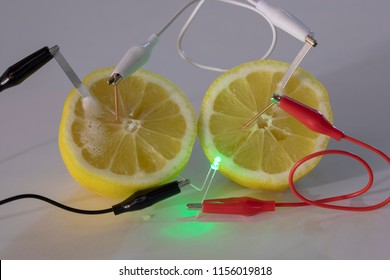 Close up of science experiment showing copper and magnesium probes in lemon connected with alligator clips on cables producing electricity to power an LED.