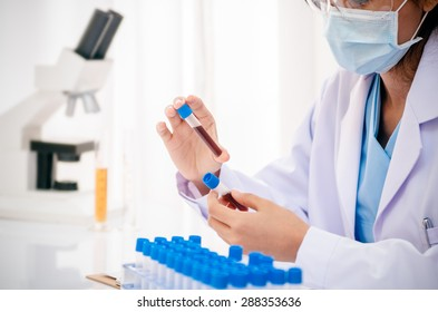 close up of scientist holding and examining blood sample in lab