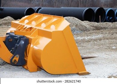 Close up of the scoop on an end loader at a construction site.