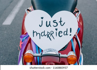 """close up of scooter with """"just married"""" heart symbol for wedding"""