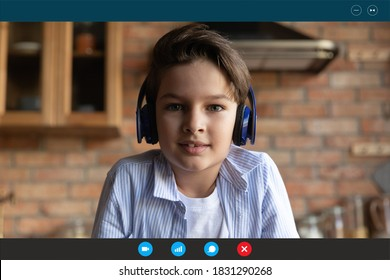 Close up screen view of cute little boy child in headphones have webcam virtual lesson or class at home. Small kid in earphones speak talk on video call, study distant. Online education concept.
