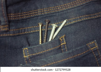Close up of screws inside the pocket of a pair of blue jeans.