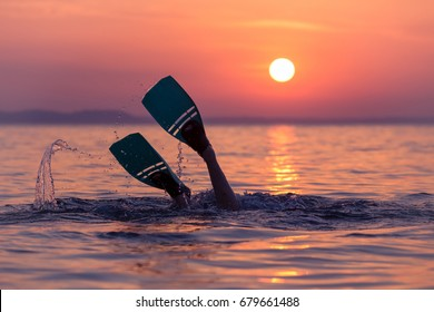 Close up of scuba diver feet with snorkel fins start diving at sunset