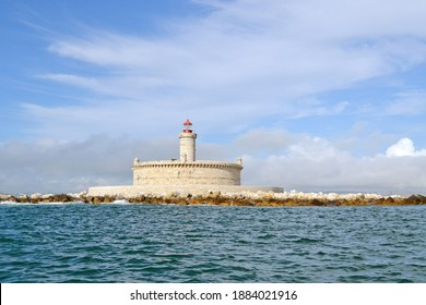 A close sea view of a light house in the middle of the ocean