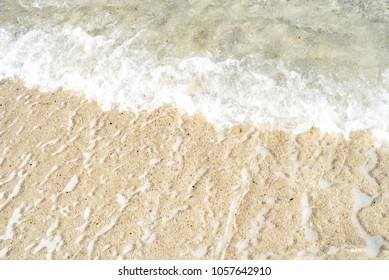 Close up sea water waves with bubbles on sand beach