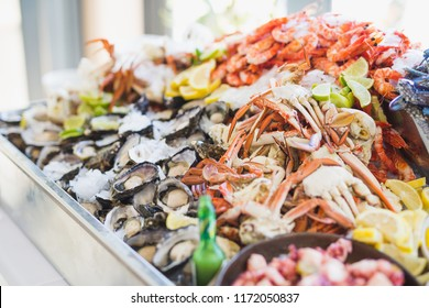 Close up of a seafood platter with prawn, crab and oyster on a bed of ice.