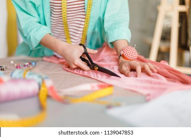 Close up seamstress cutting fabric with scissors in modern sewing workshop