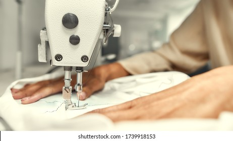 Close up of seamstress hands. She is sitting and sewing. Dressmaker working on the sewing machine. Tailor making a garment. Hobby sewing as a small business concept. Horizontal shot. Web Banner