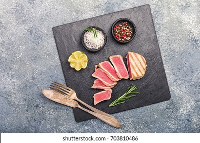 Close up of seared grilled tuna steaks on slate surface with spices and lemon, top view