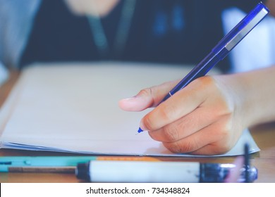 Close up secondary school girl 's hand writing on paper,do homework on wooden table in room, student  girl holding blue pen doing homework at home,or doing examination with stressed,education concept